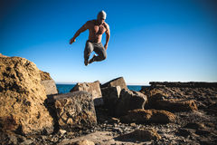 Free Man Performs Freerunning Jump On Stones Royalty Free Stock Photography - 50655107