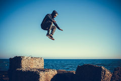Man performs freerunning jump on stones Royalty Free Stock Photography