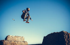 Man performs freerunning jump on stones Royalty Free Stock Images
