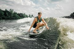 Man performs his professional abilities and skills with wakeboar. Healthy brunette man performs his professional abilities and skills with wakeboard on the Royalty Free Stock Images