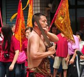 Man Performs a Ritual Sword Dance. KAOHSIUNG, TAIWAN -- APRIL 20, 2014: An unidentified man with a large sword performs a ritual dance during a local religious Royalty Free Stock Image