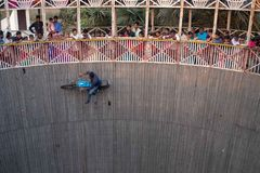 A man performs stunts while riding the wall of death at a festival surrounding NAN stock photo