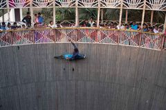 A man performs stunts while riding the wall of death at a festival surrounding NAN stock photography