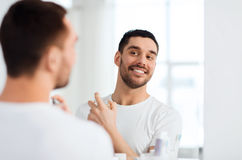 Man with perfume looking to mirror at bathroom Royalty Free Stock Photos