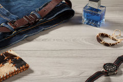 Man perfume, watch, leather purse, amulet  and blue jeans with l Royalty Free Stock Photography