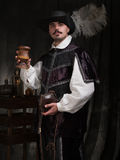 A man in period costume and hat raises a glass of wine Royalty Free Stock Image