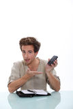 Man with a personal organizer. Young man with a personal organizer and cellphone Stock Image
