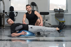 Man With Personal Trainer On Bosu Abs Exercise. Personal Trainer Showing Young Man How To Train On Bosu Abs Exercise In A Health And Fitness Concept Royalty Free Stock Images