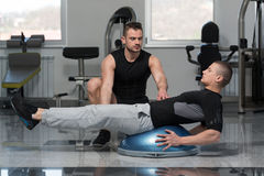 Man With Personal Trainer On Bosu Abs Exercise. Personal Trainer Showing Young Man How To Train On Bosu Abs Exercise In A Health And Fitness Concept Royalty Free Stock Photography
