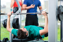 Man and Personal Trainer in gym Stock Image