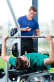Man and Personal Trainer in gym Stock Photography
