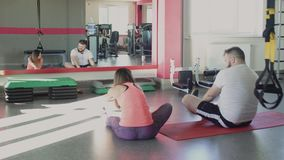 Man and personal trainer rest after training in fitness center. Thick obese guy with private slim coach do physical. Overweight male and female trainer with stock video