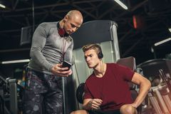 Man and personal trainer with tablet pc computer. In the gym Royalty Free Stock Images