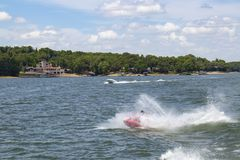 Man on Personal Water Craft landing in a spray of water after jumping a wake at the lake with speedboat and houses and boat docks. On shore in the distance Royalty Free Stock Photo