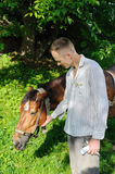 Man is petting horse. Man is standing next to a horse and stroking his head Royalty Free Stock Photos