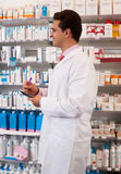 Man pharmacist at the chemists shop. Smiling man salesman with a notebook and pen in hand at the pharmacy royalty free stock image