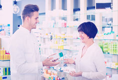 Man pharmacist helping customers in drug store Stock Photo