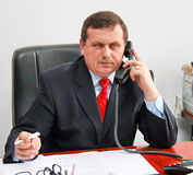 Man on phone. A man in a dark suit and red tie sits at a table in the office and talking on the phone Royalty Free Stock Photography