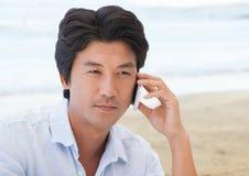 Man on phone against blurry beach Stock Photo