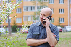 Man with phone in background of a multistory building Royalty Free Stock Photography