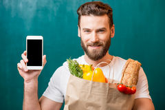 Man with phone and bag full of food stock image