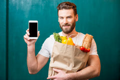 Man with phone and bag full of food Royalty Free Stock Images