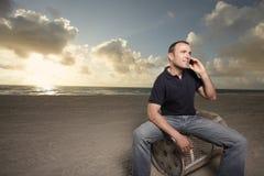 Man on the phone on the beach Stock Photos