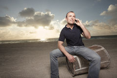Man on the phone on the beach Stock Image