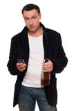Man with a phone and bottle of scotch Royalty Free Stock Image