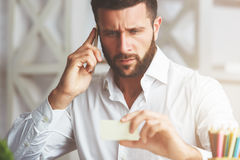 Man with phone and business card. Portrait of handsome confident european businessman talking on the phone and holding blurry business card at workplace Royalty Free Stock Photo