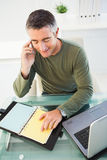 Man on the phone checking his notes Royalty Free Stock Photography