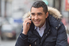 Man on the phone. Cheerful middle-aged man in winter clothing talking at phone and smiling Stock Photo