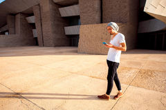 Man with phone in the city. Man dressed in white t-shirt and hat using phone near the modern grey building Stock Image