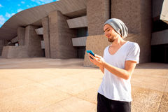 Man with phone in the city. Man dressed in white t-shirt and hat using phone near the modern grey building Royalty Free Stock Photo