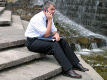 Man with phone and computer. Man listening a mobile phone holding a laptop in a park Royalty Free Stock Photography