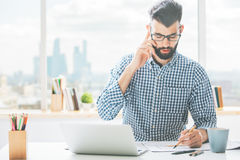 Man on phone doing paperwork Royalty Free Stock Photos