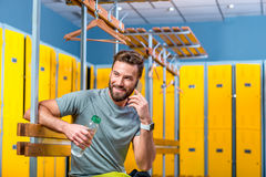 Man with phone in the gym. Handsome sports man talking with phone sitting in the locker room at the gym Royalty Free Stock Images