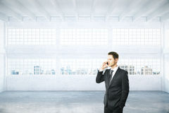Man on phone in hangar. Businessman talking on phone in empty light hangar interior with daylight and city view. 3D Rendering Stock Photo