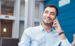 Man on phone. Happy young man on phone, indoors - inside. Close up of businessman talking on mobile phone - smartphone. Comunicative friendly hispanic man Stock Image