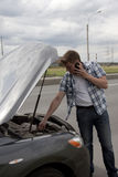 Man with phone beside his broken car. Man speaking on the phone beside his broken car royalty free stock images