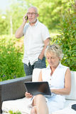 A man on phone and his wife on  computer Royalty Free Stock Photos