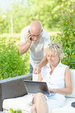 A man on phone and his wife on  computer Royalty Free Stock Images