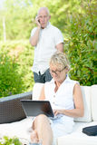 A man on phone and his wife on  computer Stock Photography