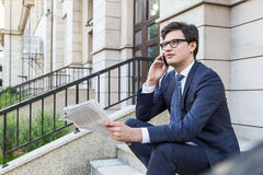 Man on phone holding newspaper Royalty Free Stock Photography