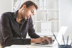 Man on phone keyboarding Stock Photo