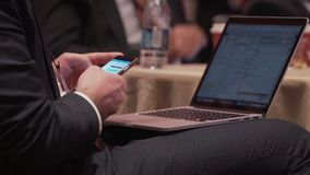 Man with phone and laptop at a conference stock video