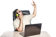 Man with a phone and laptop. Man with glasses sitting near laptop and holding a mobile phone Royalty Free Stock Photography
