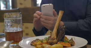 Man with phone making photo of a served dish stock video footage