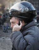 Man with a phone. Man in a motorcycle helmet with a mobile phone during street protests Stock Photography