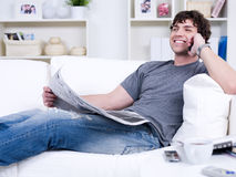 Man with phone and newspaper. Smiling handsome man with phone and newspaper - lying at home Stock Image
